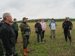 Foto 1: Fälträff vid Thomas Jakobsson (i mitten) med bra uppslutning. Regnet hängde i luften men vi klarade oss undan de värsta regnskurarna. På bilden står vi vid kanten av hans ekopotatisskifte och diskuterar hur hantera potatisbladmöglet i ekopotatisen. Thomas Snellmans franska gäst berättade att i Frankrike sprutas olika kopparlösningar för att skydda blasten. I Finland finns inga godkända kopparpreparat som kan användas för att bekämpa möglet.